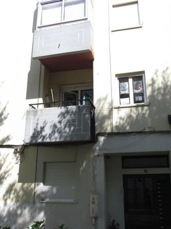 A varanda da sede, com vassouras e panos pendurados, no 1 andar, lado esquerdo.